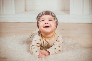 Bebé con gorro sonriendo en la alfombra