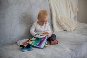Bebé en el sofá con un libro de tela