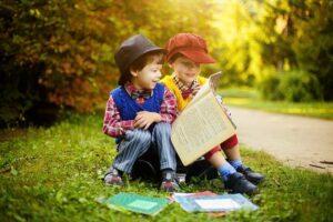 Niños leyendo libros en el césped del parque