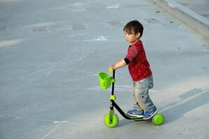 Niño con camiseta roja y patinete verde en la calle