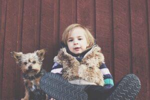 Niño sentado al lado de un perro