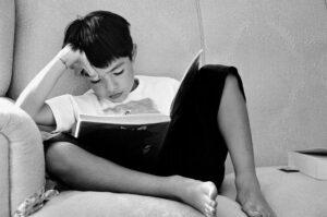 Niño leyendo un libro en el sofá en blanco y negro