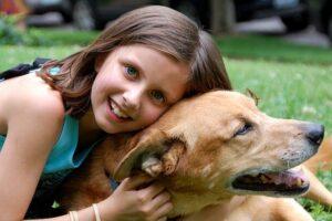 Niña abrazando a un perro y sonriendo en el parque