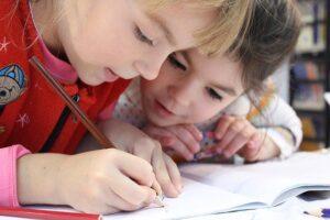 Niño y niña estdiando y escribiendo en una libreta
