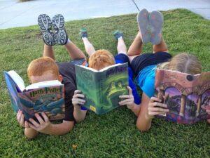 Tres niños leyendo Harry Potter en el césped