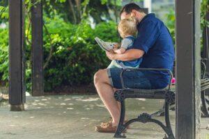 Niña sentada en el regazo de su padre mientras le cuenta un libro en el banco del parque