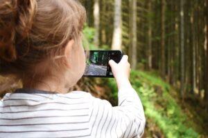 Niña haciendo una foto del bosque con un móvil