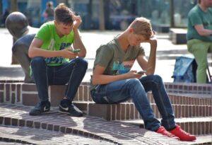 Chicos sentados en una plaza jugando con el móvil