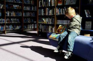 Niño sentado en la biblioteca leyendo un libro