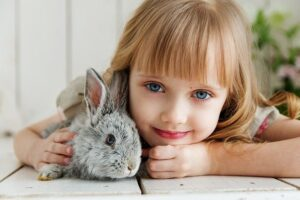 Niña abrazando a un conejo gris en el suelo de madera blanca