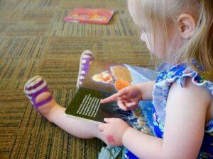Niña sentada en el suelo señalando un libro