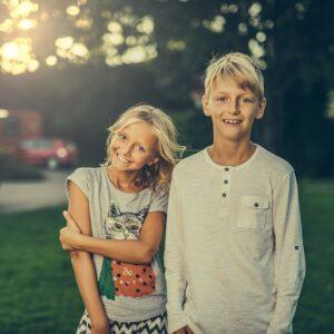 Hermanos sonriendo en el parque detrás de la puesta de sol