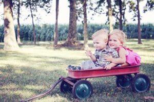 Niños en el parque jugando con una carretilla roja
